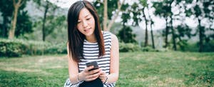 Young woman sitting outside on the grass, looking up how does a savings account work on her cellphone