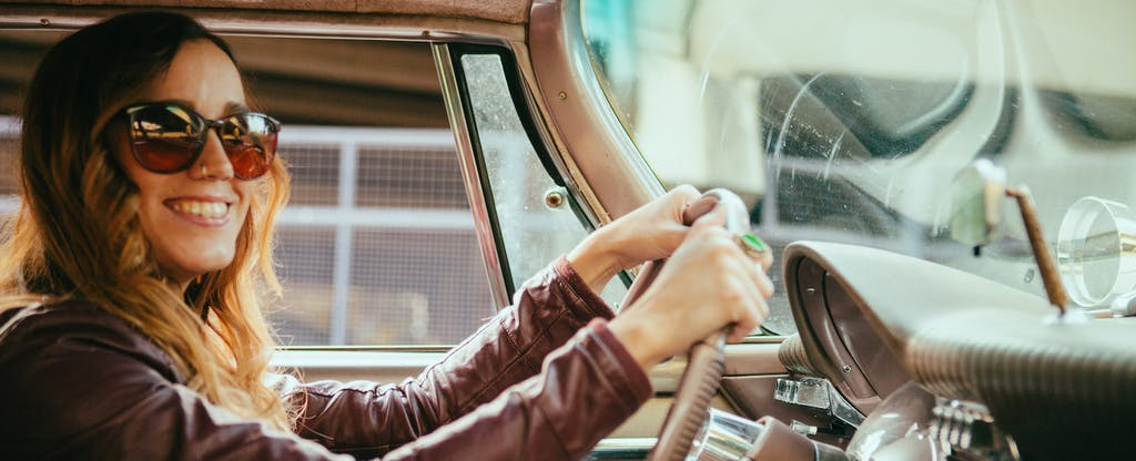 woman driving car and smiling