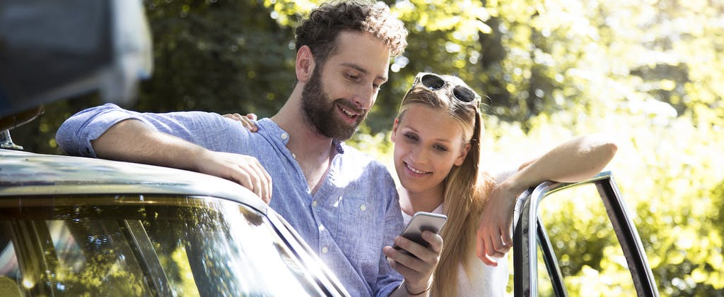 Smiling young couple with cellphone standing by car in the woods