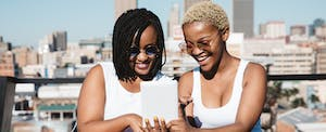 Two smiling women outside, looking up penfed personal loans on digital tablet