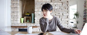 Woman sitting at table leaning on elbow looking at paperwork