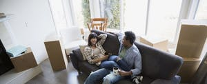 Couple sitting in living room, surrounded by moving boxes