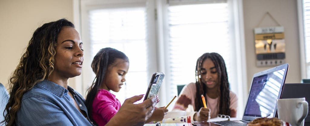 mother working on device with kids at dining table