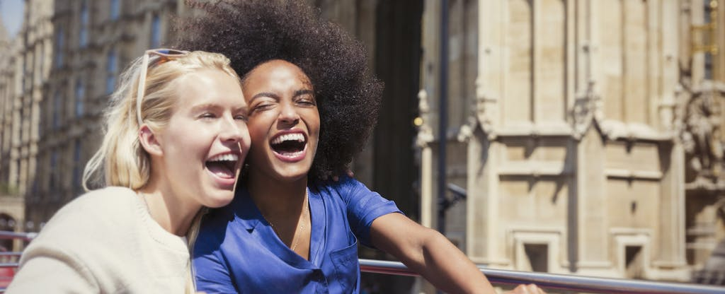 Two young women sitting on an open top double-decker bus, laughing together as they enjoy a tour of London
