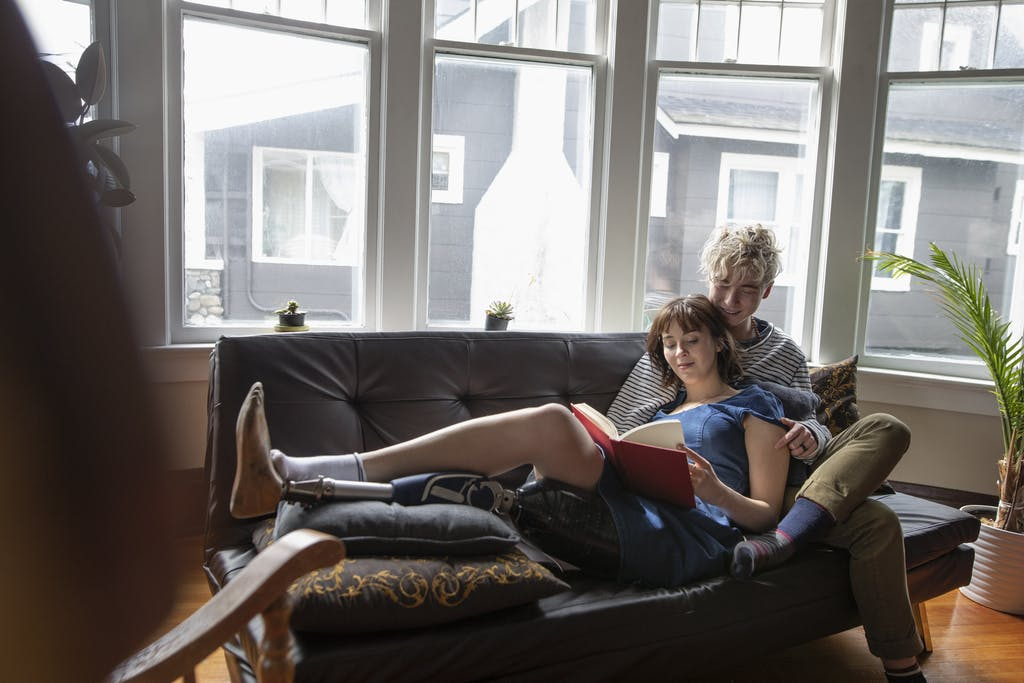 Young man and woman sitting together on their couch at home, smiling add reading a book together