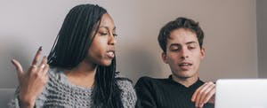 Young man and woman sitting together at home, reviewing their finances together