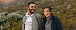 couple smiling with countryside in background