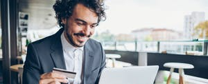 man holding credit card smiling with laptop