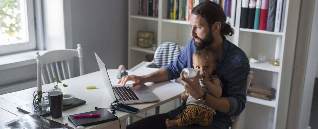 A single father sits at his kitchen table, with his infant son on his lap, considering buying a home as a single parent.