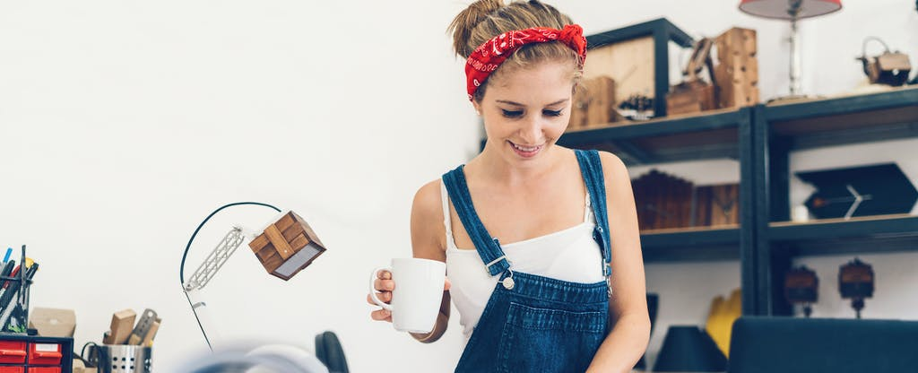 woman wearing overalls holding a coffee cup