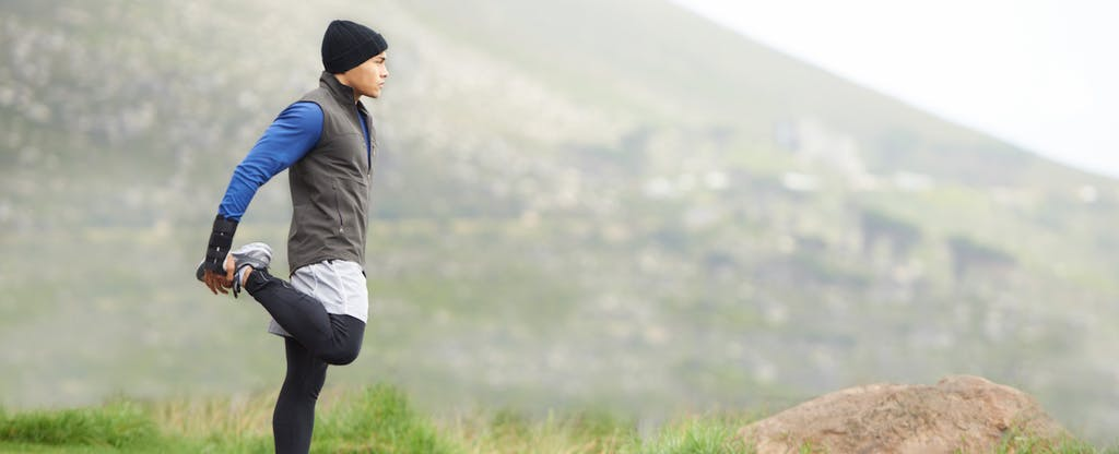 Young man in warm athletic clothes stretches before a run.