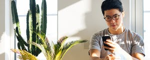 Young man with smartphone, sitting on the floor at home with houseplants