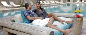couple lounging by pool with cocktails