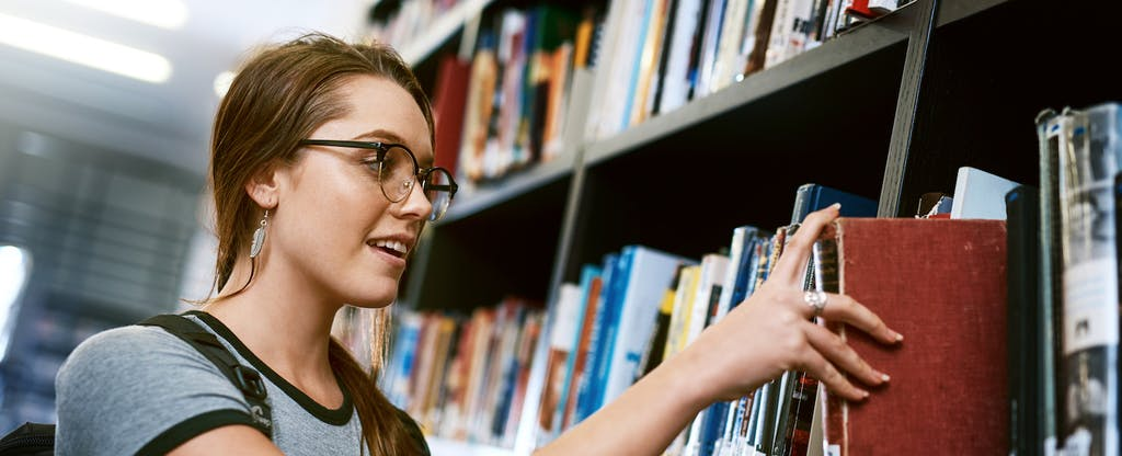 Shot of a happy young woman removing a book from a shelf in a college library