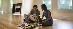 two women looking at paint samples in new empty house