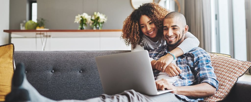 Man and woman sitting at home together, sitting on the couch and reading on their laptop about VA loans