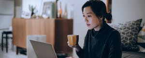 Woman holding mug while on her laptop concentrating