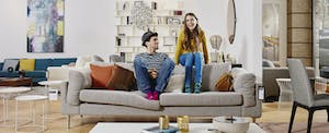 Couple in modern furniture store sitting on couch, laughing