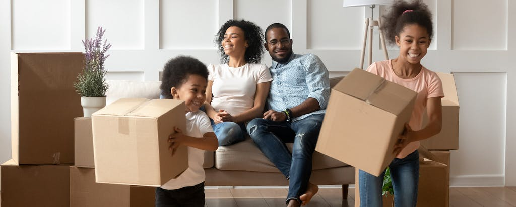 Happy parents and kids in home with moving boxes