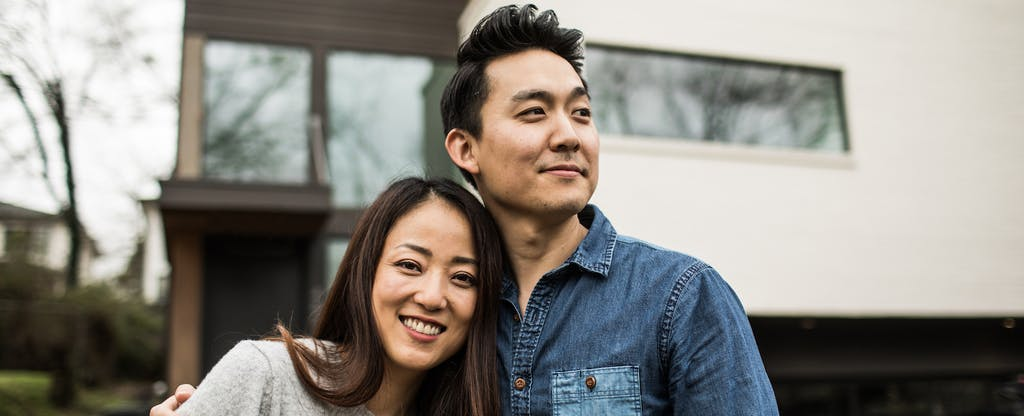 Man and woman standing outside of their new home that they purchased with a Flagstar mortgage