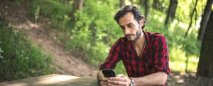Young man using a phone while sitting in the park