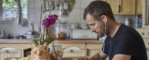 Man sitting at his kitchen table with his cat, working on his laptop as he closes on his Guaranteed Rate mortgage from home