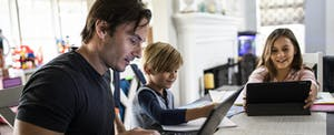 Father on laptop at home with kids